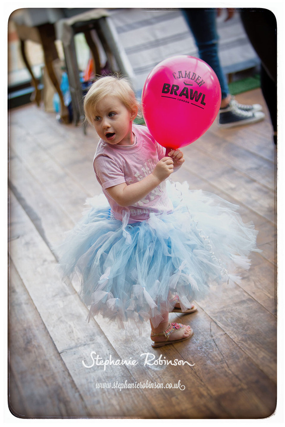Little girl holding balloon wearing Camden Brawl t-shirt